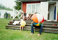 Fahter and daughter inflating beach balls, Blekinge, Sweden.