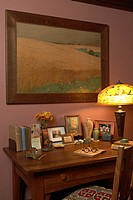 LIVING ROOM: Arts and Crafts style home, desk area with reverse painted shade on metal lamp, books, family photos, eye glasses, ink well, oak frame