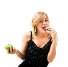 Frau isst Schokoriegel statt Apfel