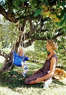 Mother watching son on swing