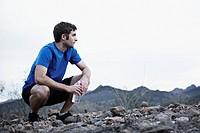 Man on mountain holding water bottle