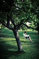 Woman reading book under tree in garden