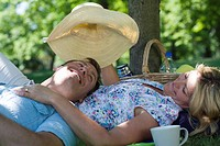 A couple lying on a blanket in a park, woman lifting a hat placed over the man's head, Sweden.