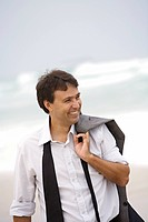 A smiling man walking on the beach, Brazil.