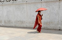 nepalese lady holding red umbrella taking a walk, kathmandu, nepal