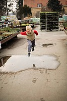A blond boy jumping over a puddle of water, Sweden.