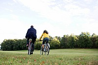 A woman and a man riding a bike an autumn day, Sweden.