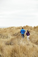 Couple exercising in long grass by sea