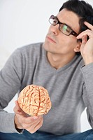 Man holding model brain, thinking
