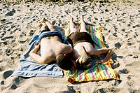 A couple lays next to each other in the sand