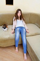 Portrait of a young blond woman in jeans lying on sofa