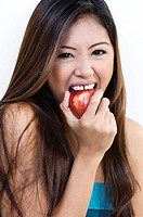 Studio portrait of young woman biting apple