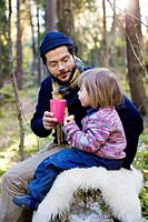 Father and daughter eating lunch in forest