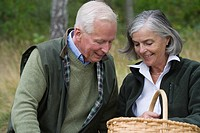 Senior couple holding basket, smiling