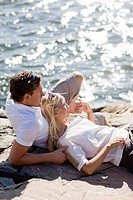 Couple lying on rock beside sea