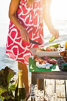 Woman standing by table on jetty, preparing food