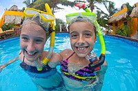 Caucasian girls snorkeling in swimming pool
