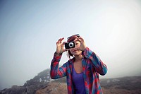 Korean woman taking photograph with digital camera