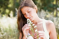 Serene woman smelling flowers outdoors