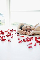 Smiling woman laying on floor with flower petals
