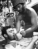WORLD WAR II: MARINE, 1944.A wounded U.S. Marine, tended by a Navy corpsman, awaiting evacuation from Bougainville, New Guinea, during World War II, 1...