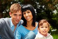 Glückliche Familie mit Tochter sitzt im Park