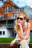 Junge blonde Frau mit Sonnenbrille sitzt auf Mauer