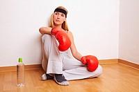 Junge blonde Boxerin sitzt entspannt auf dem Boden