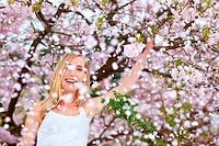 Junge blonde Frau schüttelt Ast eines Kirschbaums im Frühling