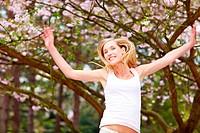 Junge blonde Frau unter einer Japanischen Blütenkirsche Prunus serrulata