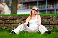 Junge blonde Frau mit Sonnenbrille sitzt auf Wiese an Mauer gelehnt