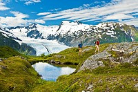 A couple hiking and enjoying the view of Portage Glacier at Portage Pass, Chugach National Forest, Southcentral Alaska, Summer