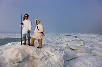 Male and female Inupiaq Eskimo hunters wearing their Eskimo parka´s Atigi carry a rifle and walking stick while looking out over the Chukchi Sea, Barr...