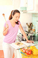 Smiling woman in domestic kitchen looking at cookbook while holding wooden spoon