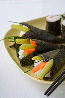 Gelber Teller mit vegetarischen Temaki und Maki Sushi. Selective focus image of a yellow plate with different kind of sushi