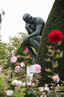 the thinker statue with roses and shrubs in the gardens, paris, france
