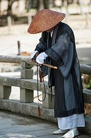 a person in a robe and conical hat at the todaiji temple, nara, japan