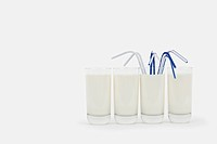 Glasses of milk in a row with drinking straws