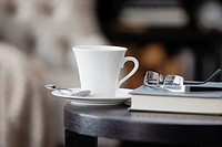 Teacup on side table with book and eyeglasses