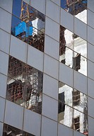 Construction equipment reflected in the windows of an adjacent skyscraper