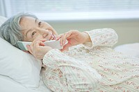 Senior woman lying on bed talking on cell phone, Kanagawa Prefecture, Honshu, Japan