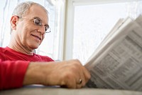 Middle aged man reading the newspaper