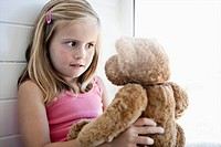 Girl staring at teddy bear