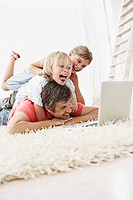 Father and children looking at laptop