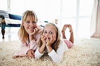 Mother and daughter lying on rug