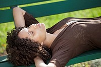 Young woman lying on a park bench