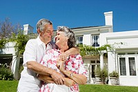 Senior couple embracing in front of house