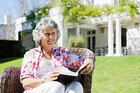 Senior woman sitting in garden with book