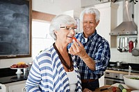 Senior man giving bite of food to senior woman