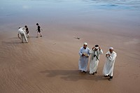 Photograph of three Moroccan men doing a treditional dance on the beach of the Moroccan city of Essaouira